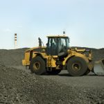 Earthmoving vehicle loading coal at a industrial site