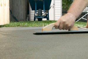 A person finishing wet cement with a concrete screed in a backyard, DIY home project themed image.