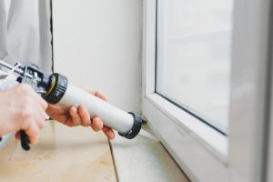 Hands of worker using a silicone tube  for repairing of window indoor